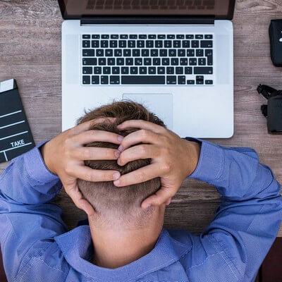 Fájdalmakkal küzdő, fáradt férfi fogja a fejét a laptop felett