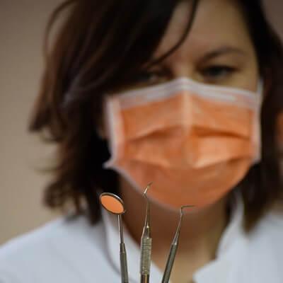 Fogorvos kezében fogorvosi eszközökkel